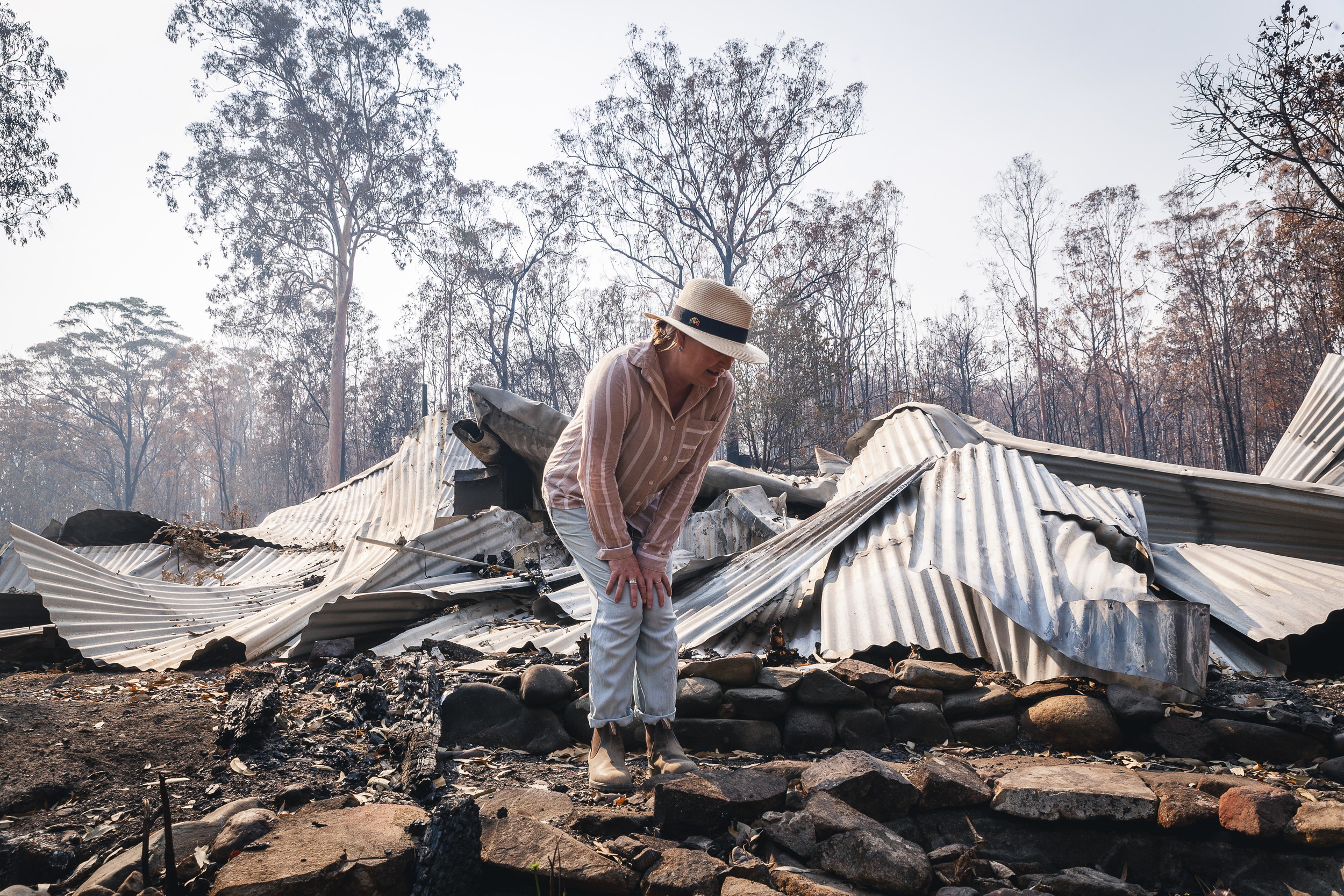 A woman examines the singed ground and remnants of her house which lays collapsed behind her