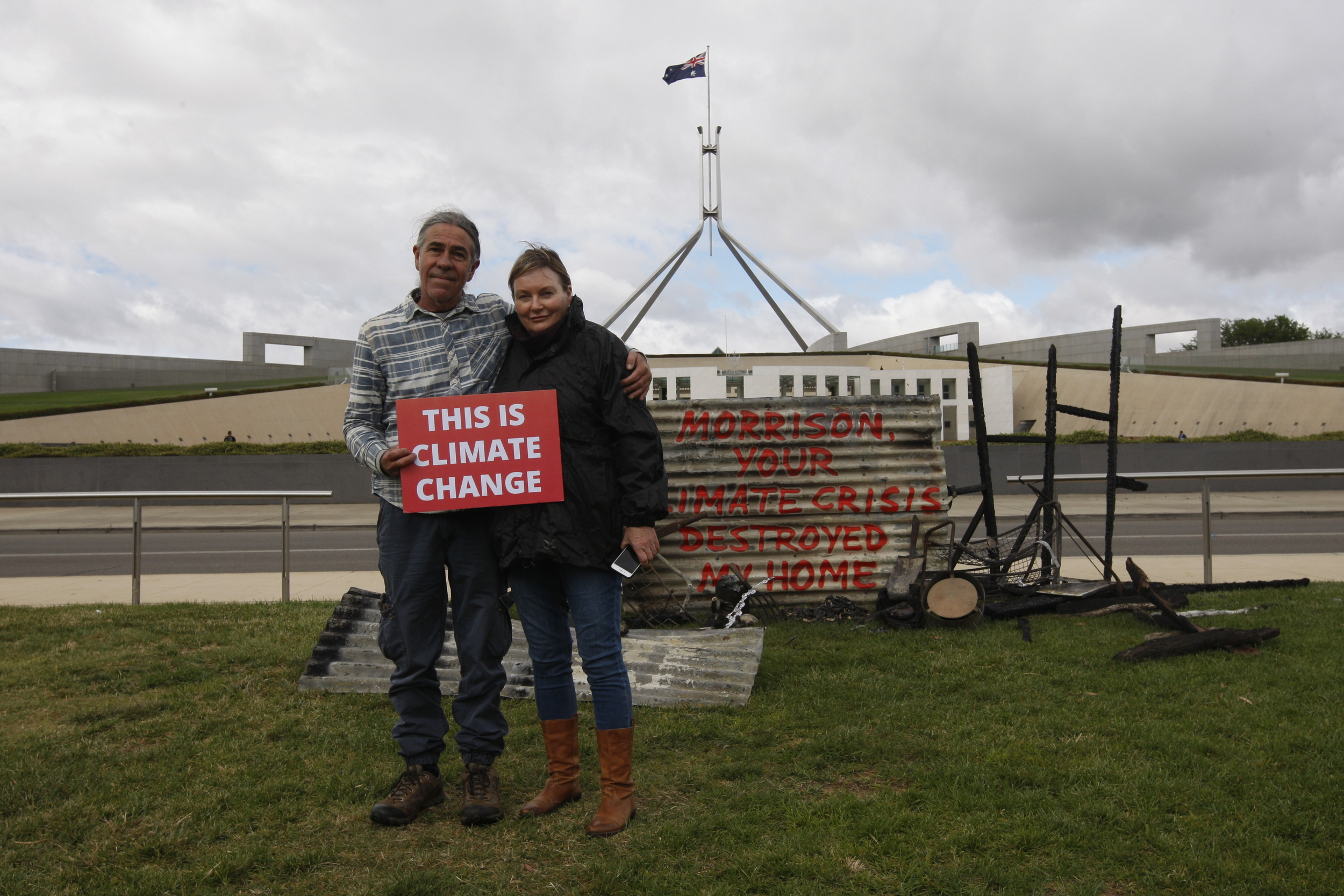 "Two bushfire survivors standing in front of Australia's parliament, with a burned roof reading ""Morrison, your climate crisis destroyed my home"" and holding a sign saying ""This is climate change"""