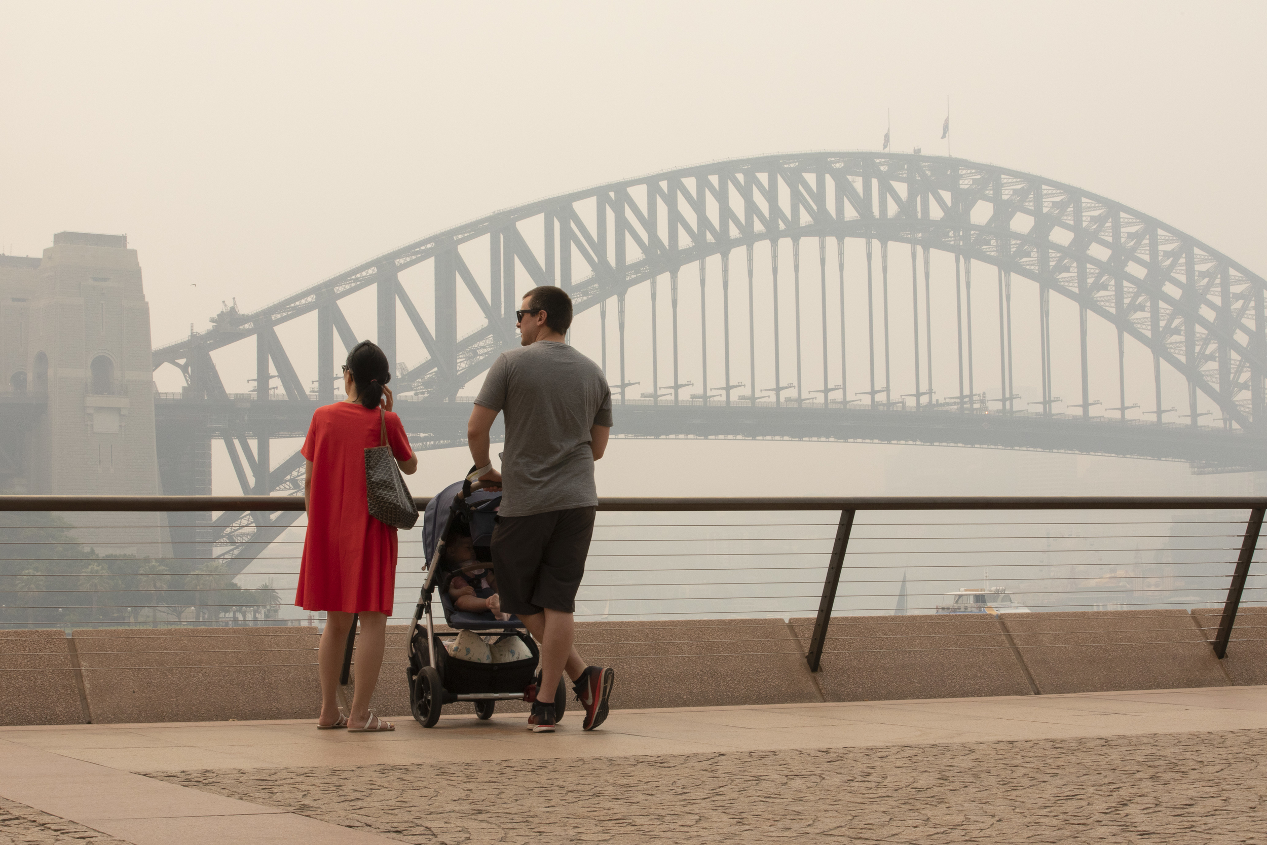 A couple with a pram look over a haze-filled Sydney harbour with the iconic Sydney Harbour Bridge just visible.