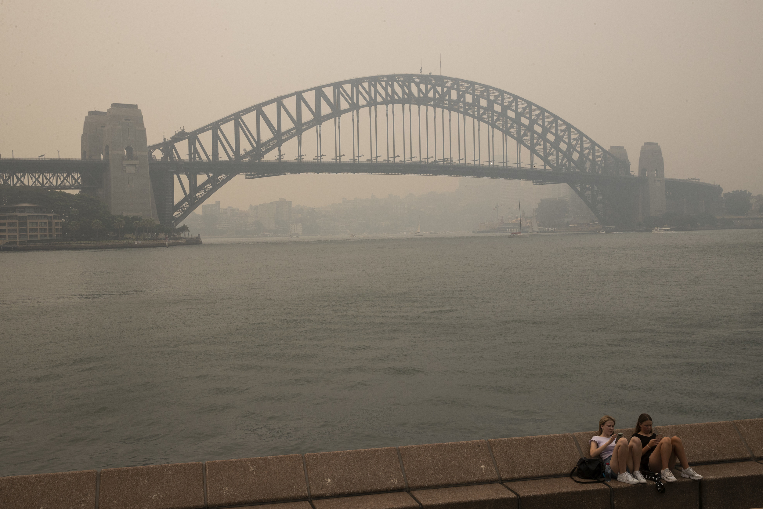 Two girls sit on a bench overlooking Sydney Harbour Bridge, which is shrouded in smoke haze from bushfires.