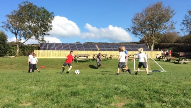 Pupils at Georgeham Primary in Devon play football in front of the school's new solar panels