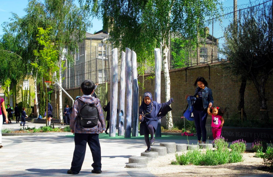 Children playing on Van Gogh Walk in London, with trees, play equipment and a basketball hoop in the background.