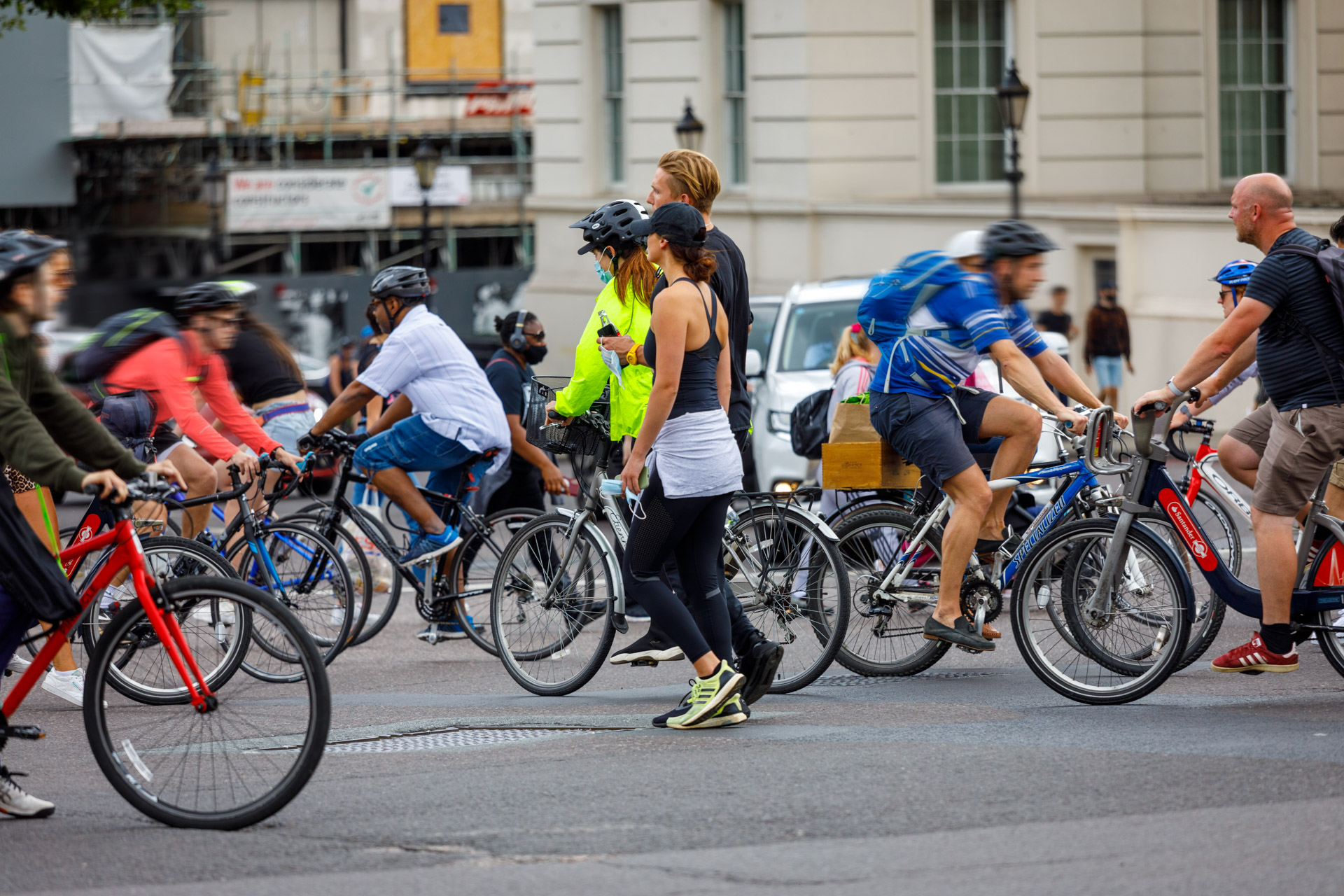 A large group of people on bikes cross a city junction in both directions