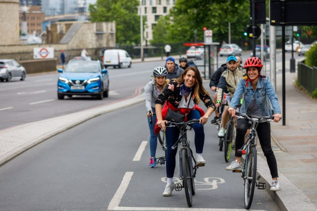 Two women on bikes smiling at the camera while waiting at a red light on a separated cycle lane. A queue of other riders is out of focus behind them.