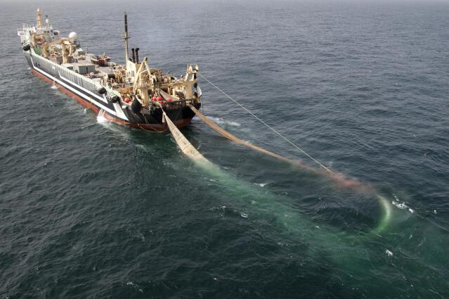 Aerial view of a giant fishing ship with a net trailing behind it