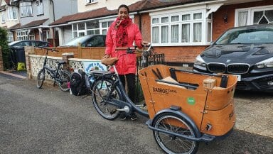 A woman stands in front of a house with her cargo bike, smiling and looking into the camera
