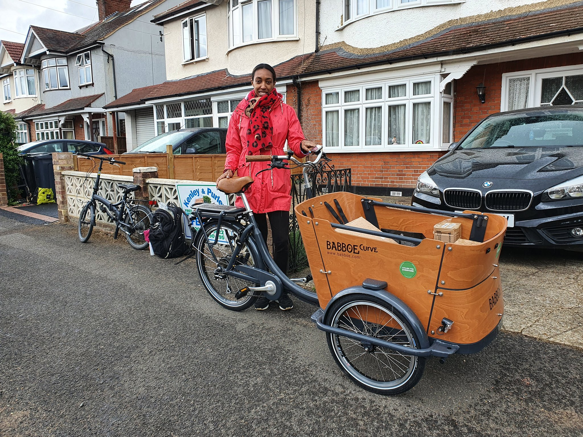 A woman stands in front of a house with her cargo bike, smiling and looking into the camera. Using cargo bikes for short trips around town is greener than either a petrol or electric car.