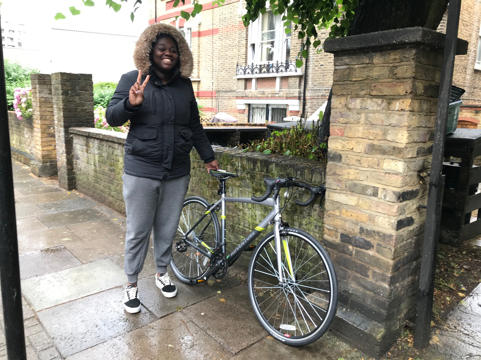A woman stands on the pavement of a city street with a new road bike alongside, smiling at the camera and flashing a peace sign
