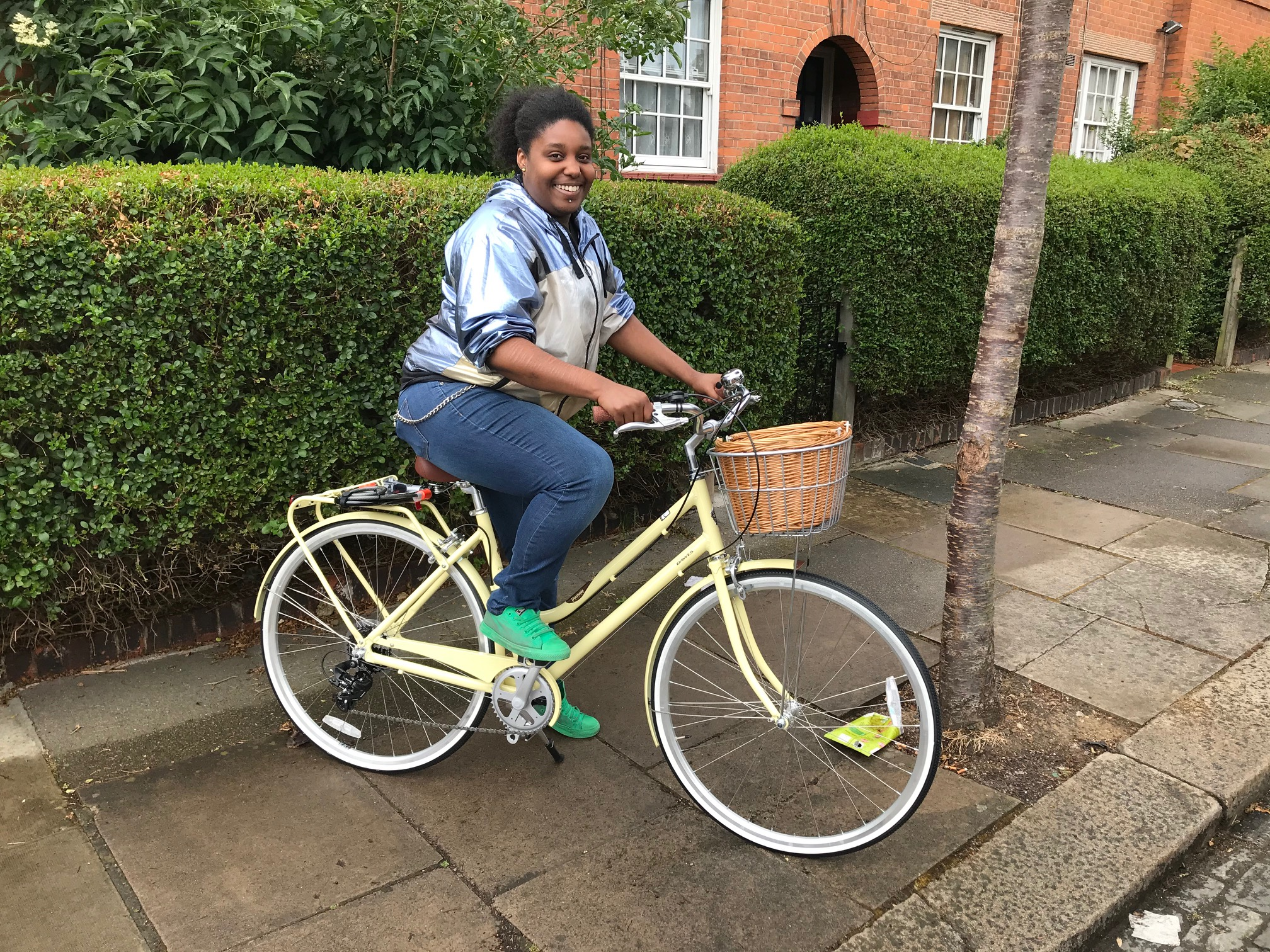 A woman sits on a dutch-style bike with a basket on the front, smiling at the camera
