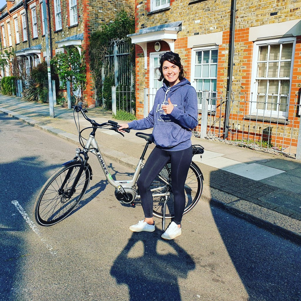 A woman stands in the street with an electric bike, smiling at the camera and giving a thumbs-up