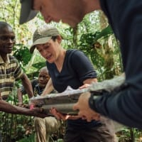 In a lush tropical forest, four people work together to position a piece of scientific equipment.