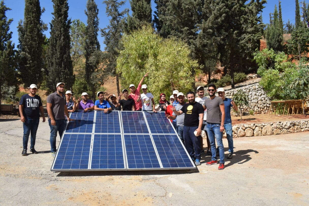 A group of people gathered around a small ground-mounted solar array, smiling at the camera.