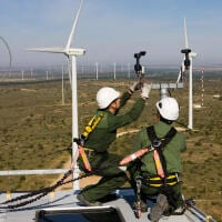 Technicians inspect equipment on the top of a wind turbine. A just transition would help workers find good jobs in emerging clean industries.