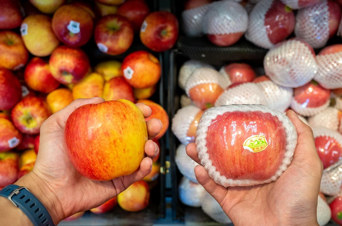 Two apples, one wrapped in plastic and polystyrene, and one loose.