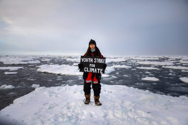 Mya-Rose Craig standing on an ice floe holding a sign reading 'Youth strike for climate'