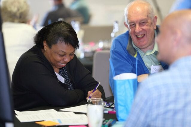 A man and a woman sit round a table smiling and laughing at the citizens climate assembly.
