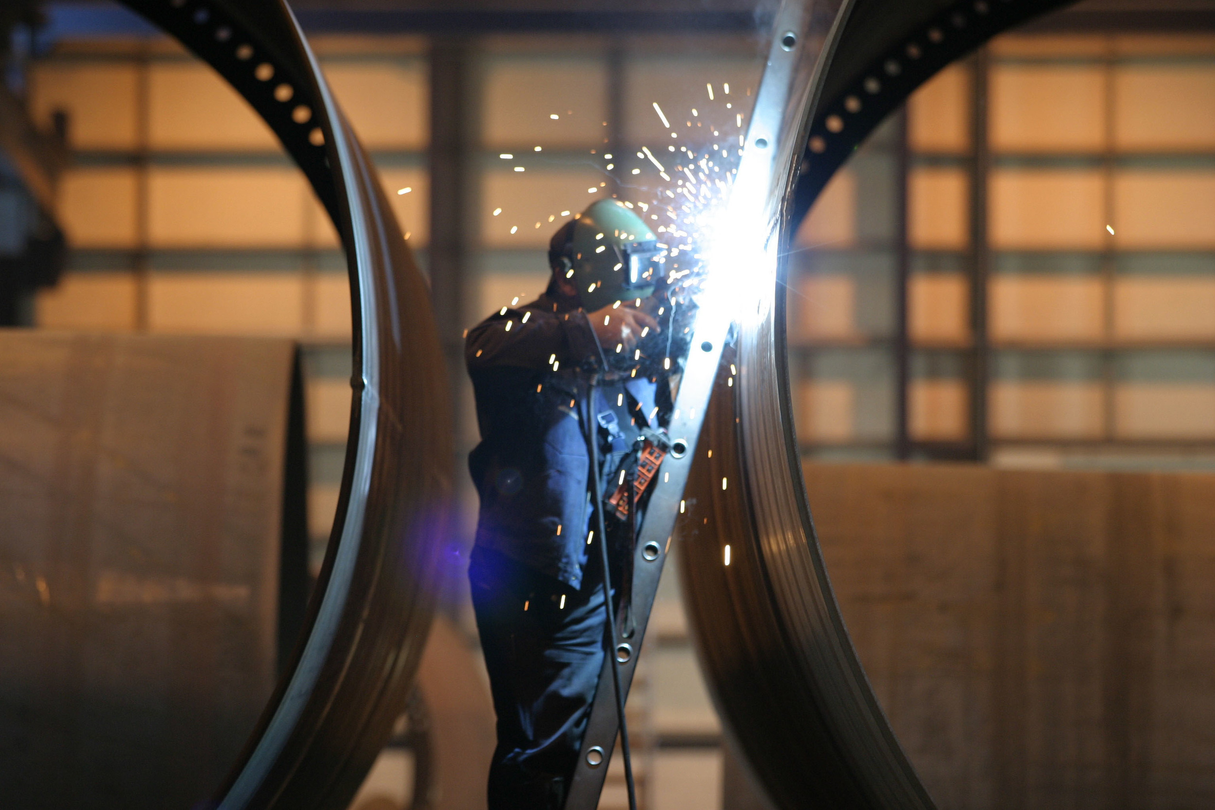 A man on a ladder welding large components of wind turbines with sparks flying