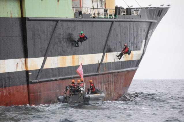 Two activists hang from the side of a large fishing ship. A small Greenpeace boat drives alongside.