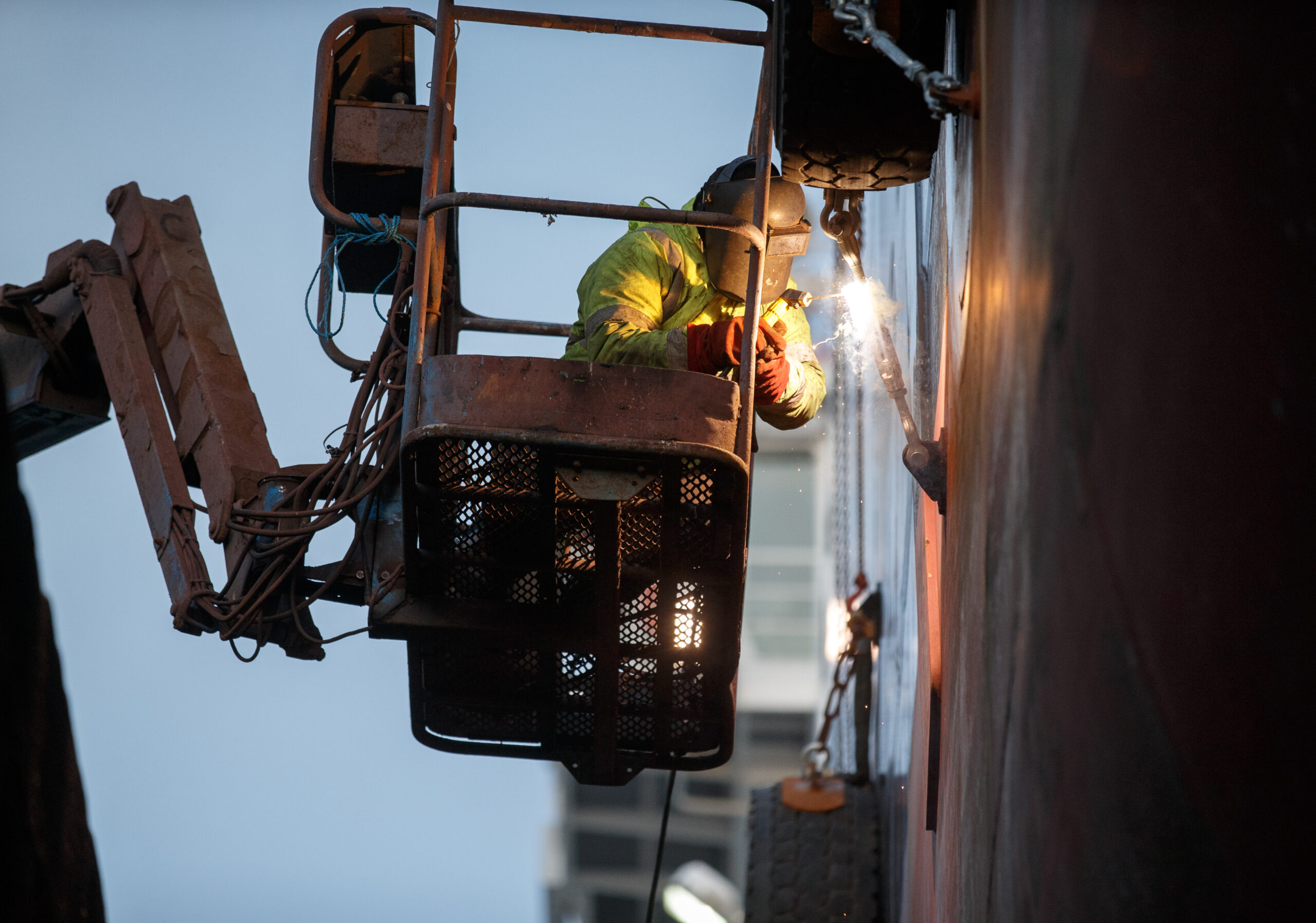 A worker on an articulated crane platform welding at the side of a rig or ship with sparks flying