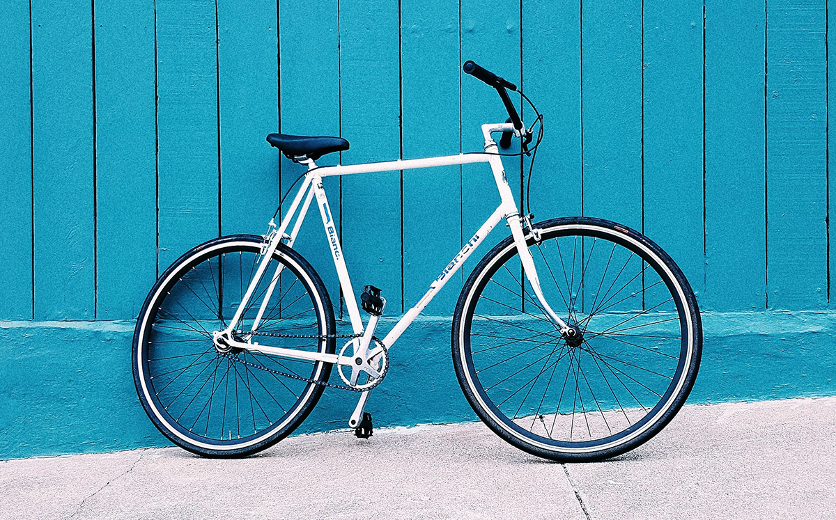 A white bike leaning against a blue-painted wall