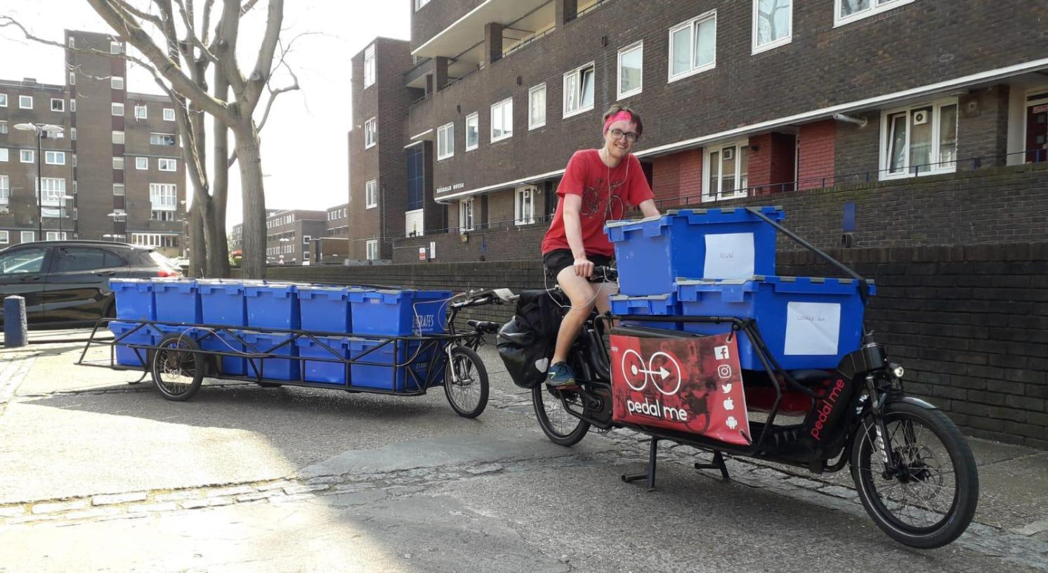 A rider carrying large plastic crates containing Covid care packages on a cargo bike with a trailer attached