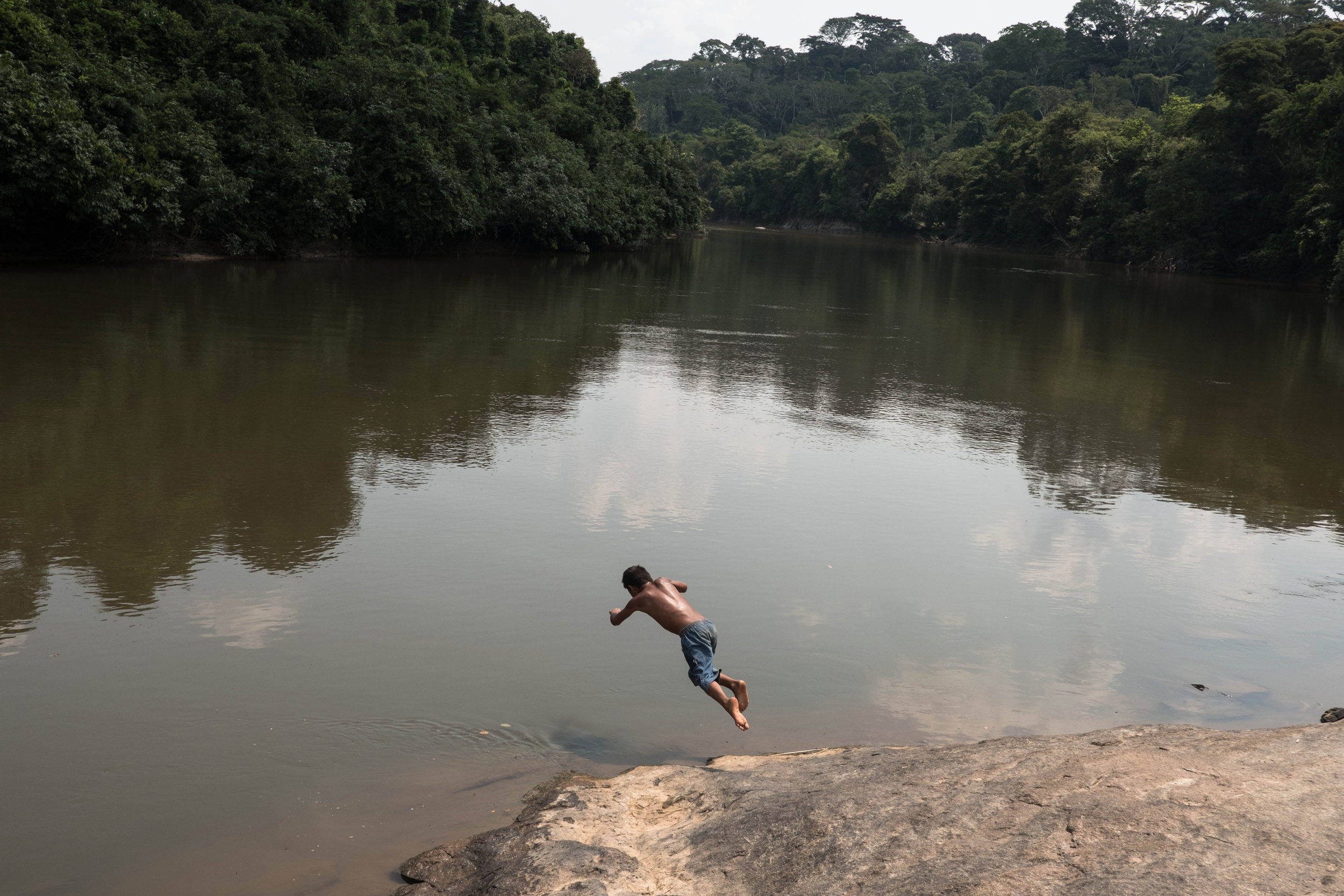 A small boy in mid-air jumping off a wide riverbank into a dark river surrounded by thick rainforest