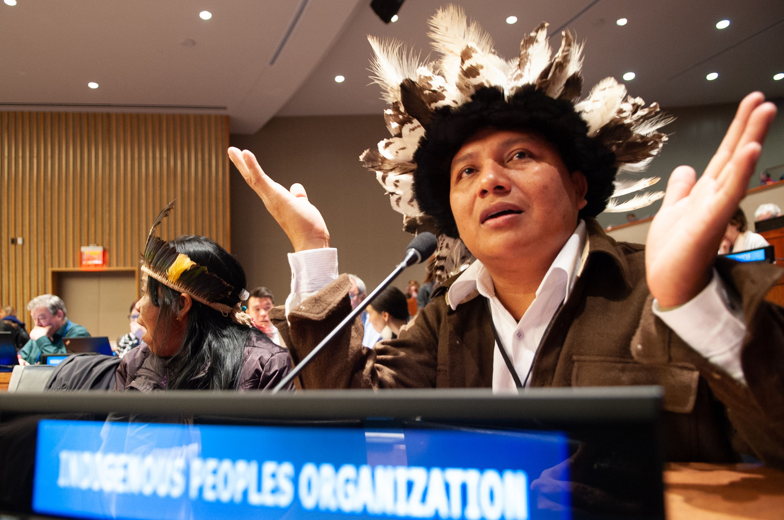Adriano in a suit and his Indigenous regalia, a headdress with balck and white feathers, sat at a desk at the UN, speaking into a microphone with his hands in the air.