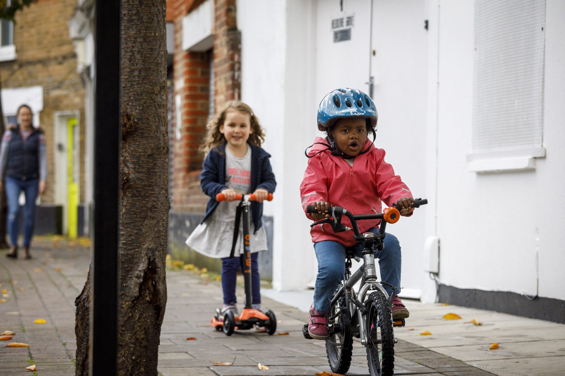 A young child on a bike rides towards the camera with a look of concentration on their face. Another child rides behind on a scooter.