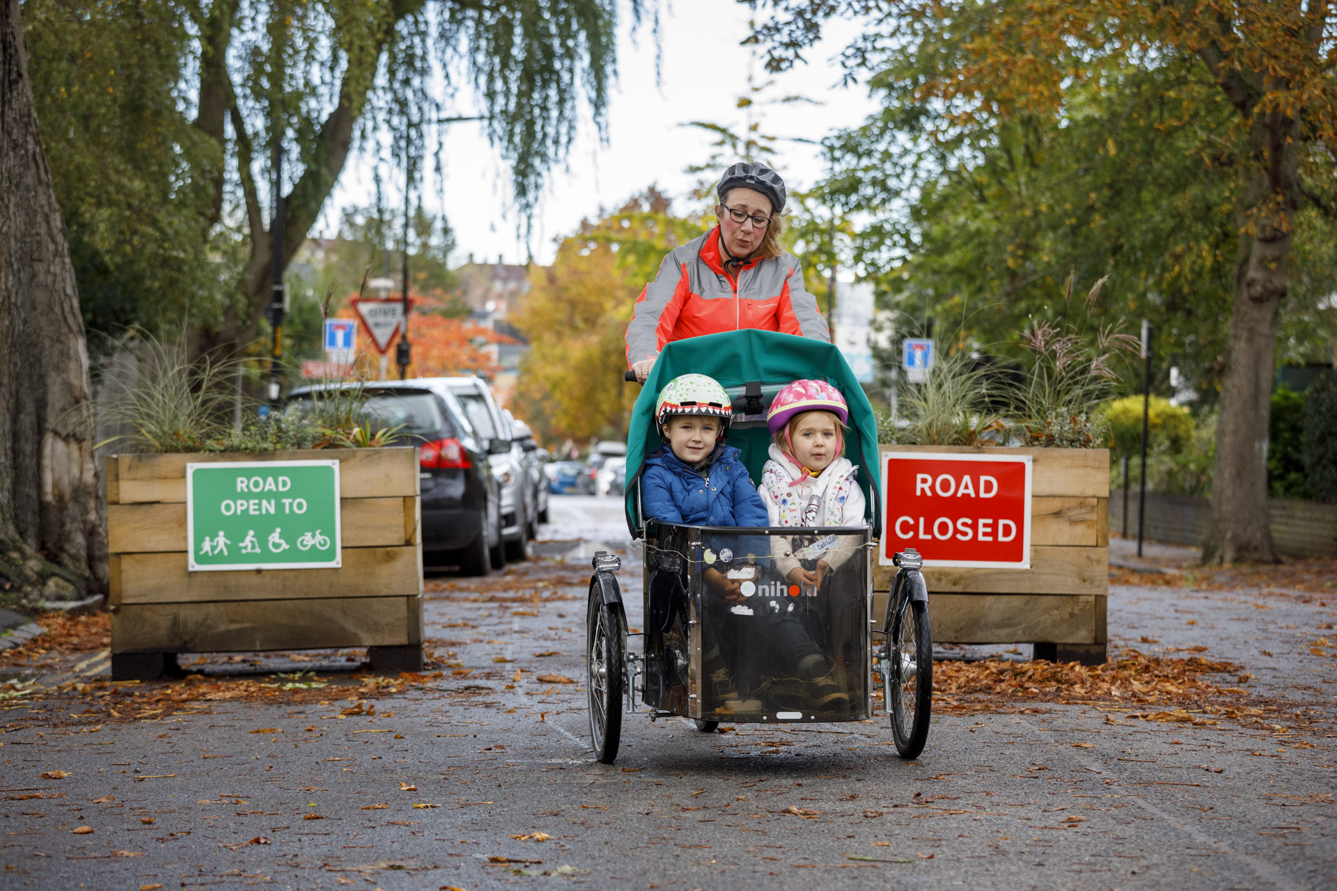An adult rides a cargo bike towards the camera, with two children sitting together in the front section. Behind them, signs attached to wooden planters announce 'Road closed' and 'Road open to bikes, pedestrians, wheelchairs, scooters etc'