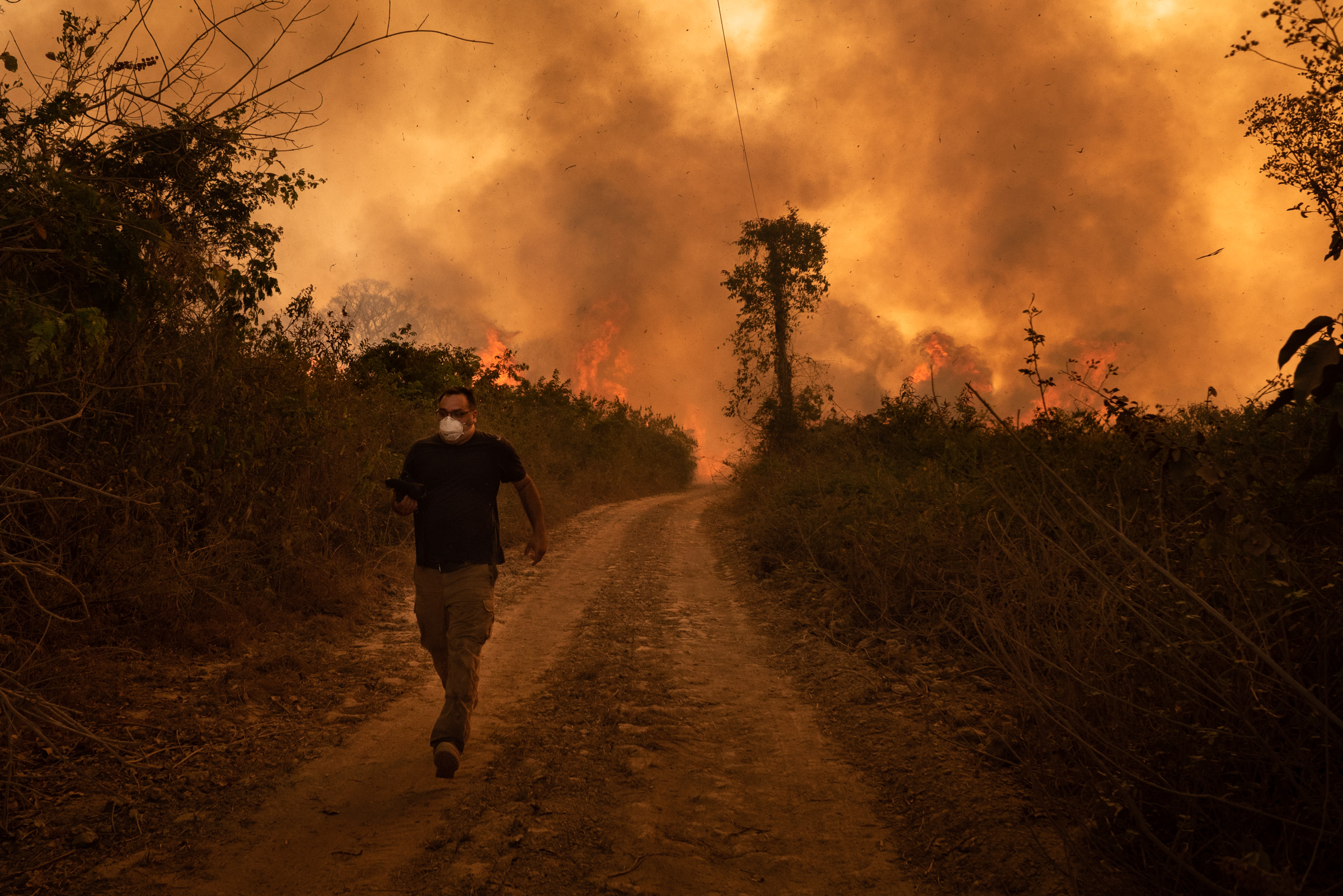 A man with a white facemask and dark clothes runs along a road towards the camera from a fire burning behind him, the whole sky yellow with smoke.