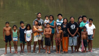 A group of around 20 adults and children stand by a river in a group, all looking into the camera. Some of the children are wet from swimming in the river.