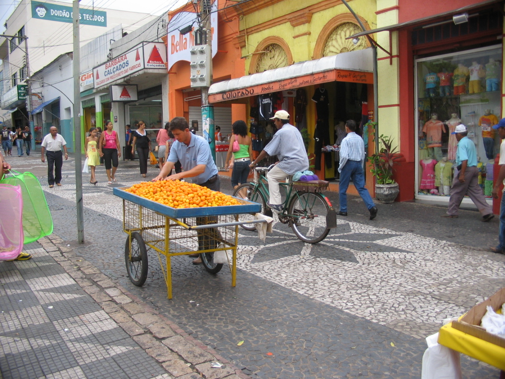 A man supervises a street stalled filled with small yellow-orange fruit. Behind him, pedestrians and cyclists pass in front of colourful buildings.