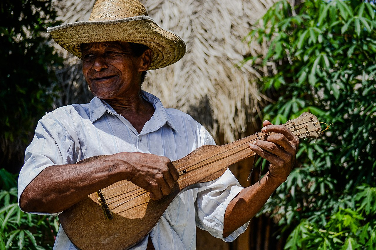 A man in a white shirt and straw hat smiles as he plays a traditional wooden string instrument