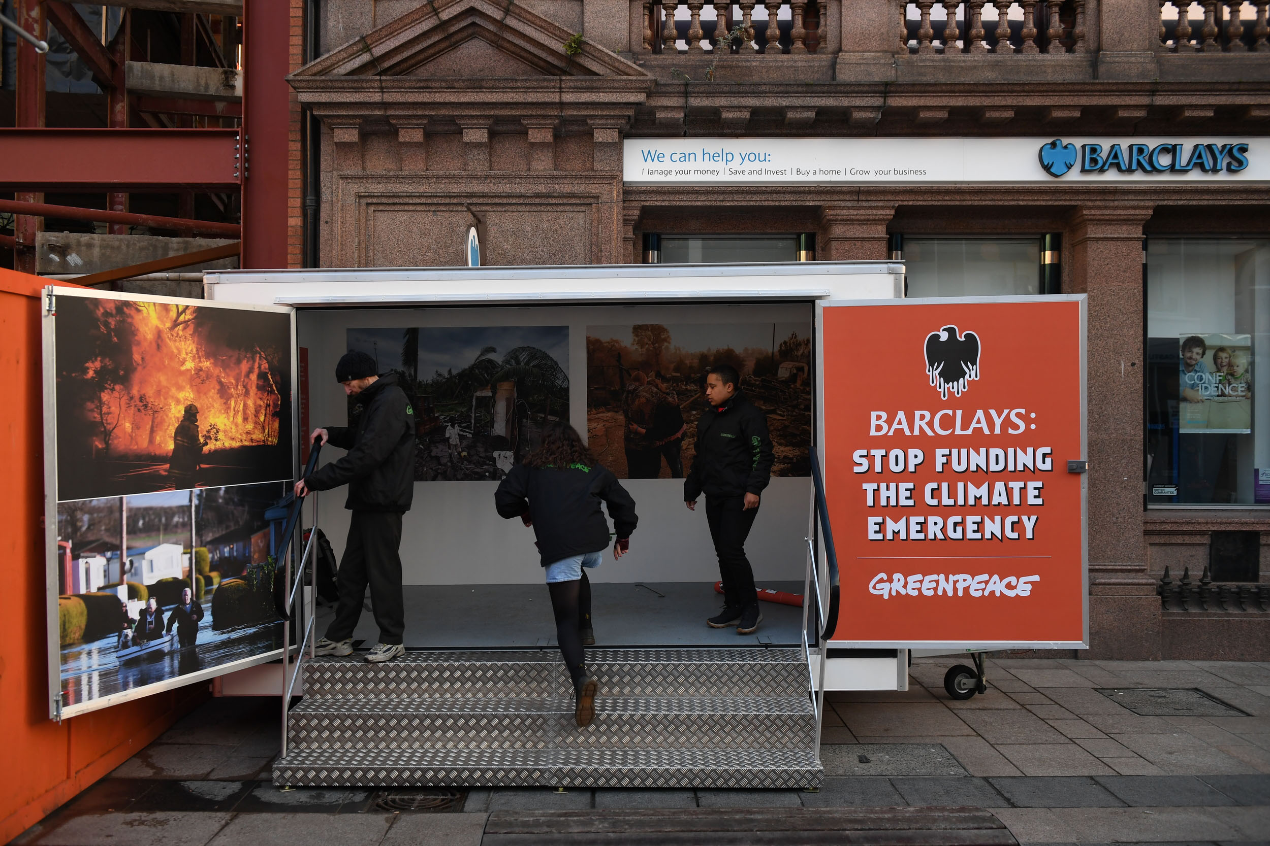 Members of the public look at photos of destruction caused by climate change, displayed in a temporary container placed in front of the entrance of a Barclays Bank branch