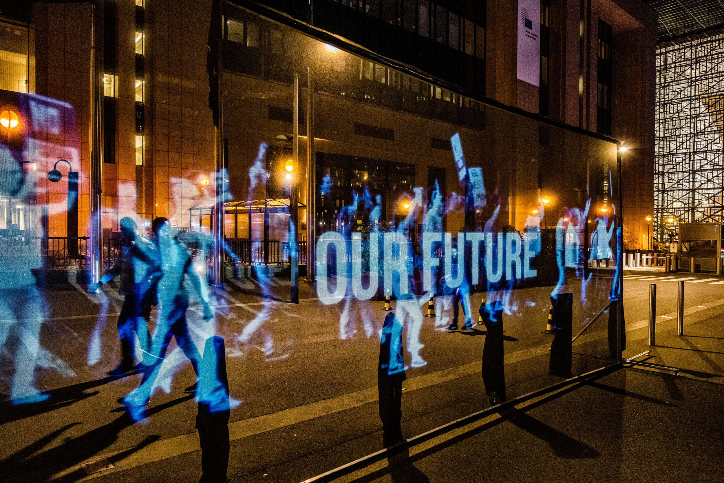 A holographic projection of people marching with a banner reading 'Our future', on a city street at night.