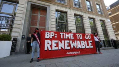 """Two activists wearing masks and red sashes stand in front of BP's headquarters holding a large banner reading """"BP: time to go renewable"""""""