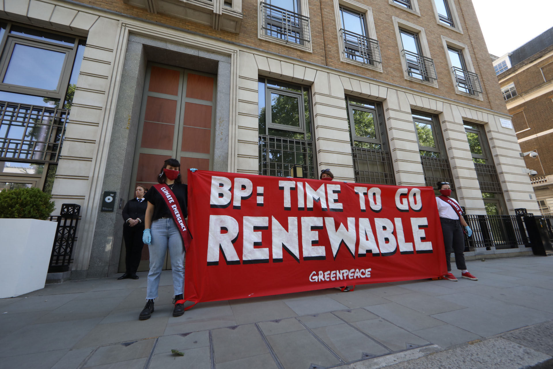 "Two activists wearing masks and red sashes stand in front of BP's headquarters holding a large banner reading ""BP: time to go renewable"""