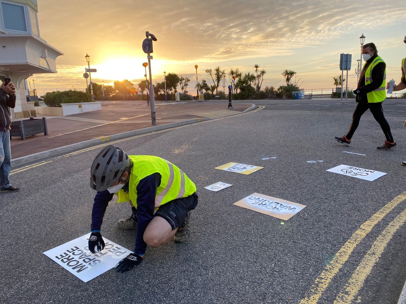 Greenpeace volunteers in fluorescent jackets apply stencils to a road surface, with a beautiful dawn sky in the background.
