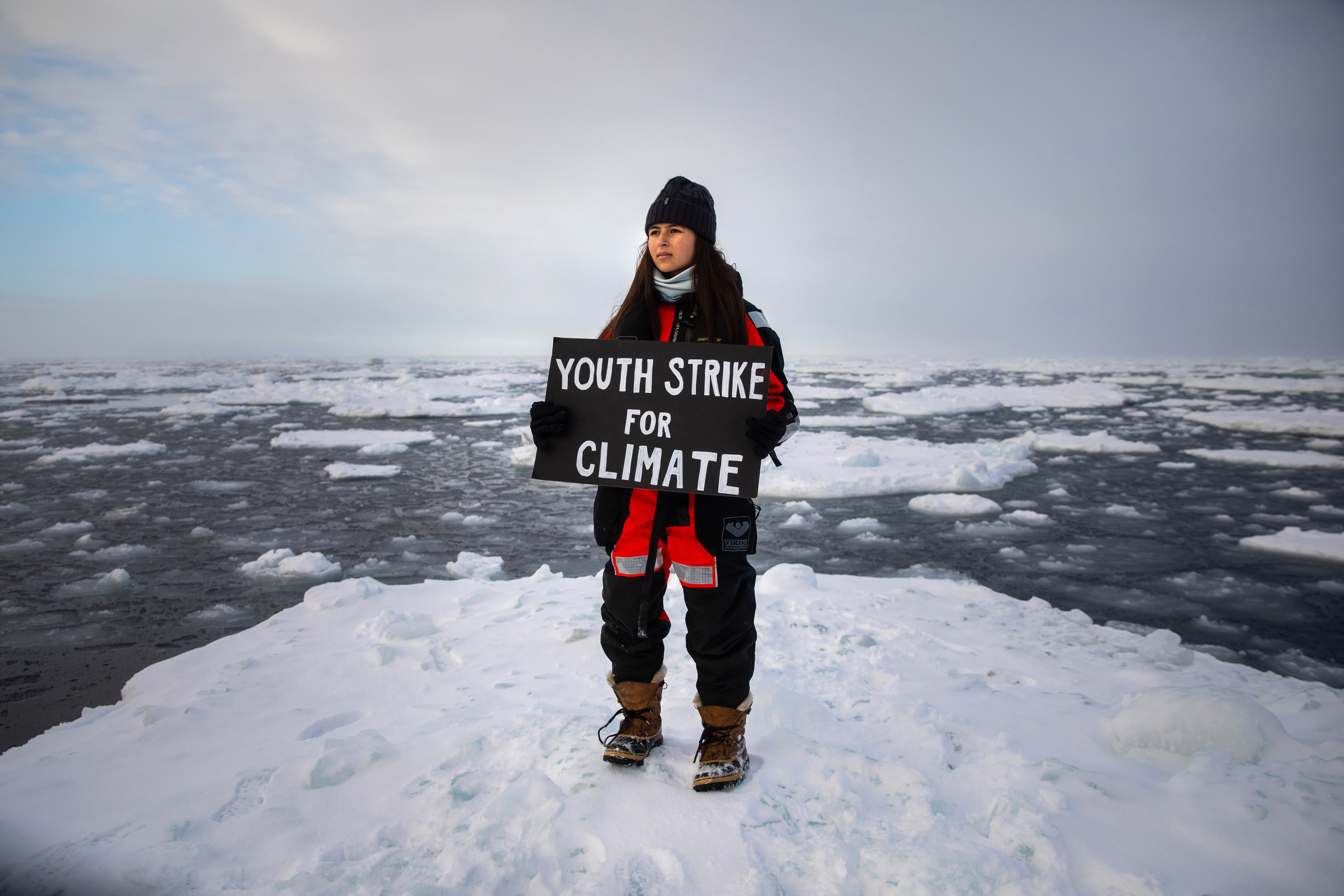 "Youth activist Mya-Rose Craig stands on an ice floe holding a hand-painted sign reading ""Youth strike for climate"""