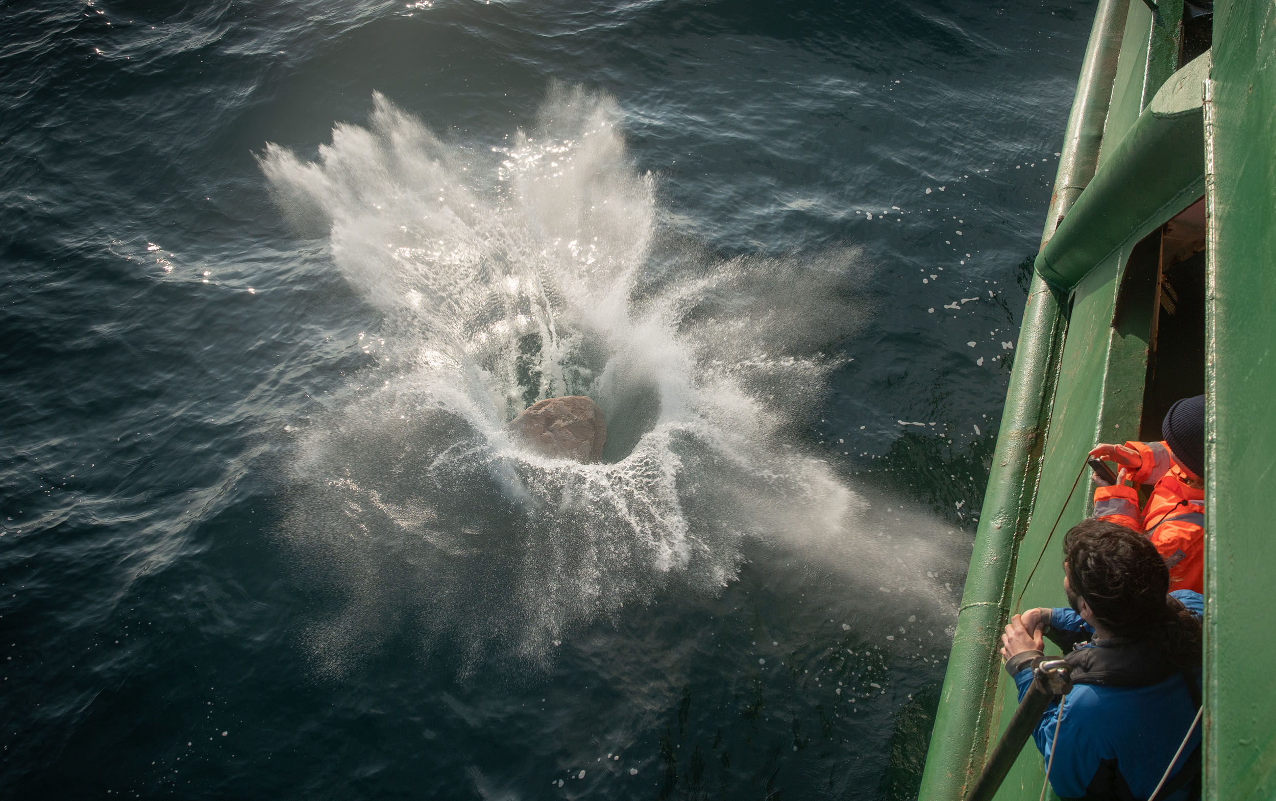 A boulder splashes into the water as crewmembers look on.