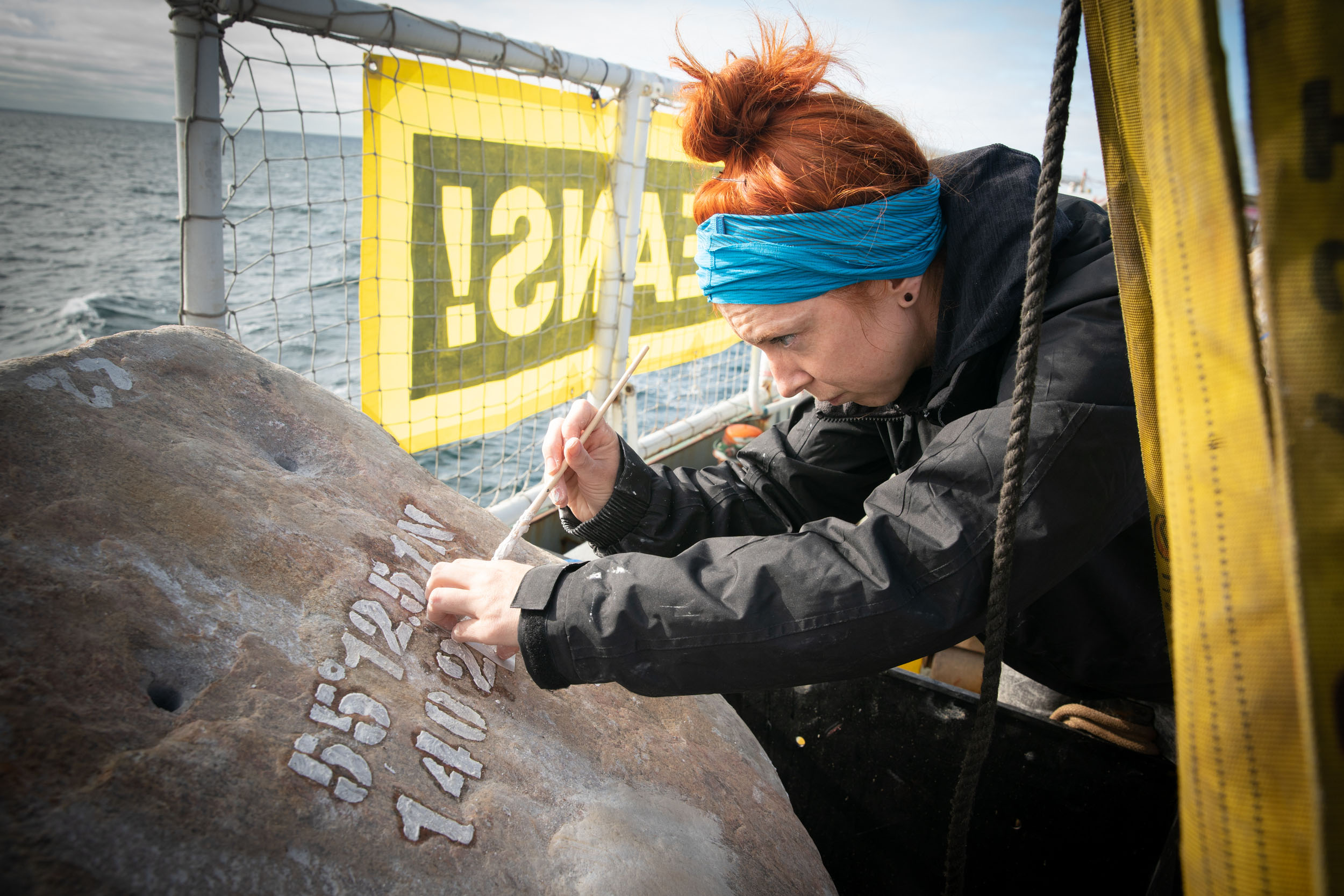 An activist paints stencilled coordinates onto a large boulder on the deck of a ship