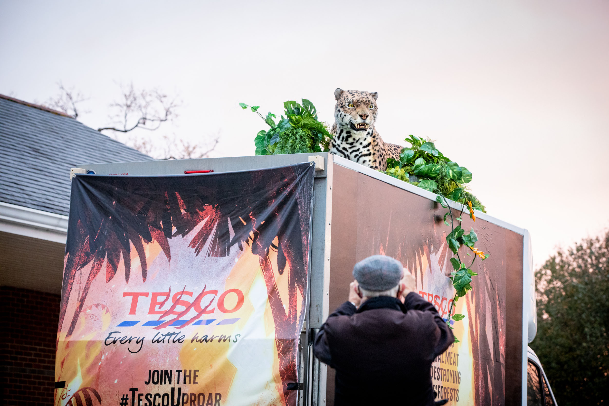 A member of the public takes a photo of a realistic animatronic jaguar sitting on top of a van branded with satirical tesco Graphics and slogans like 'Every little harms'.