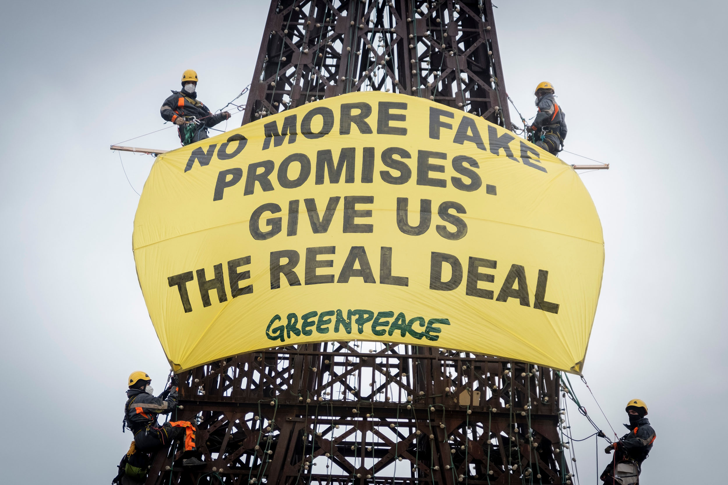 "Greenpeace climbers in masks and helmets hang from a dark latticed metal structure, displaying a large yellow banner that reads ""No more fake promises. Give us the real deal."""