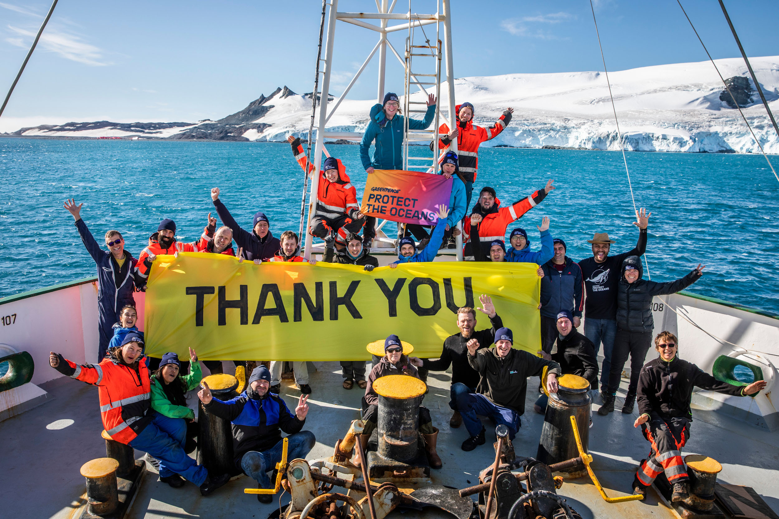 "The crew of a Greenpeace ship wave at the camera while holding a bright yellow banner reading ""Thank you"". A snowy Antarctic landscape is visible in the background."