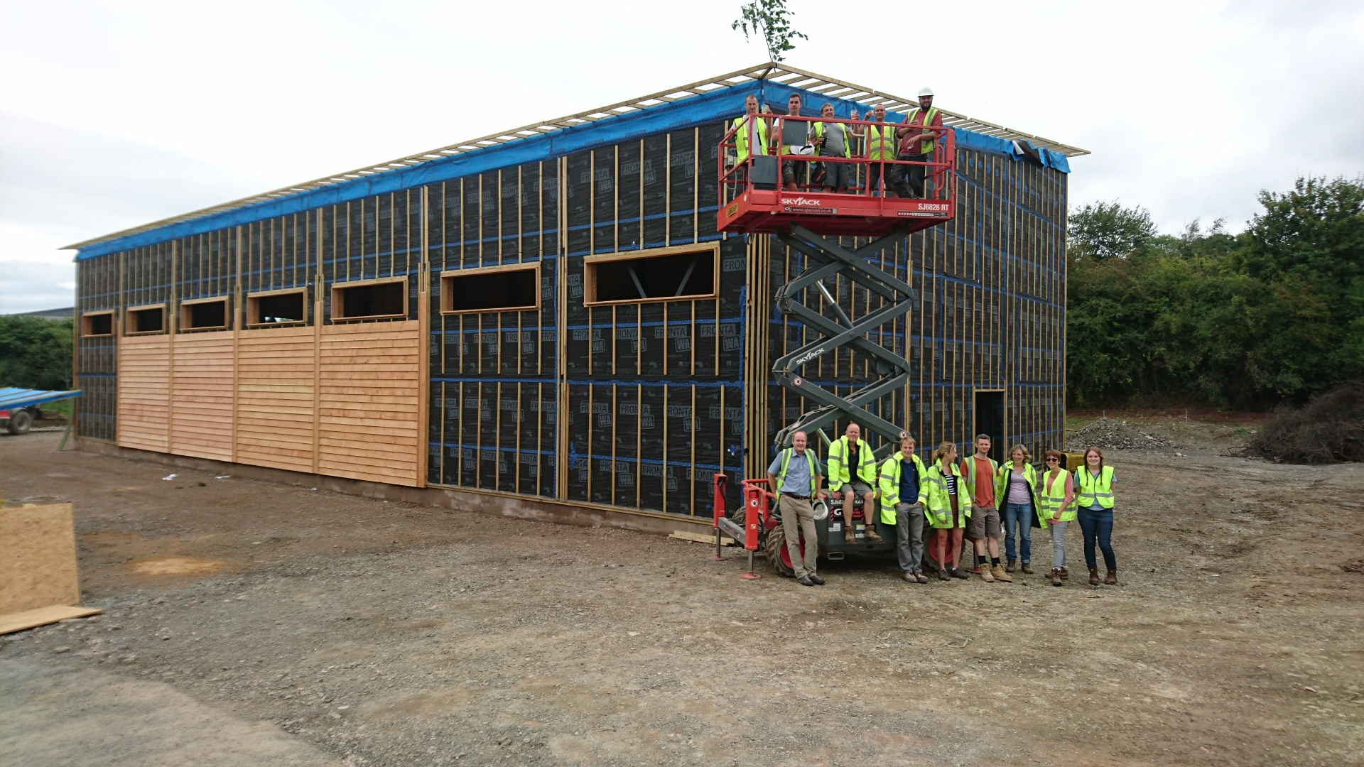 A building under construction with 14 people in front of it, 8 or so in front of an articulated lift and the others in the basket above them.