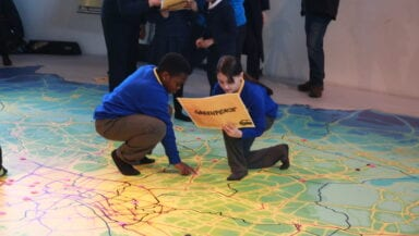 Two children crouch down on a giant floor map showing air pollution hotspots in London