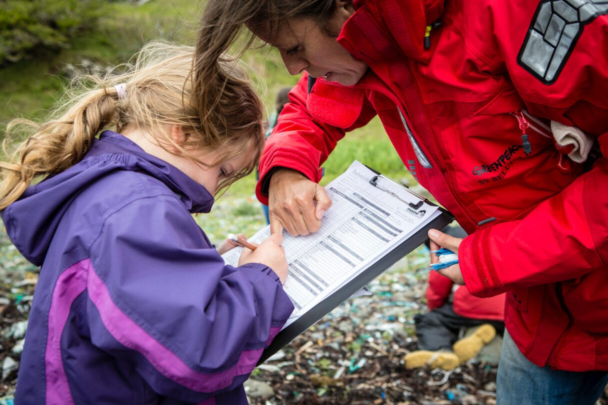 A young child dressed in a waterproof jacket examines a clipboard, while an adult looks on.