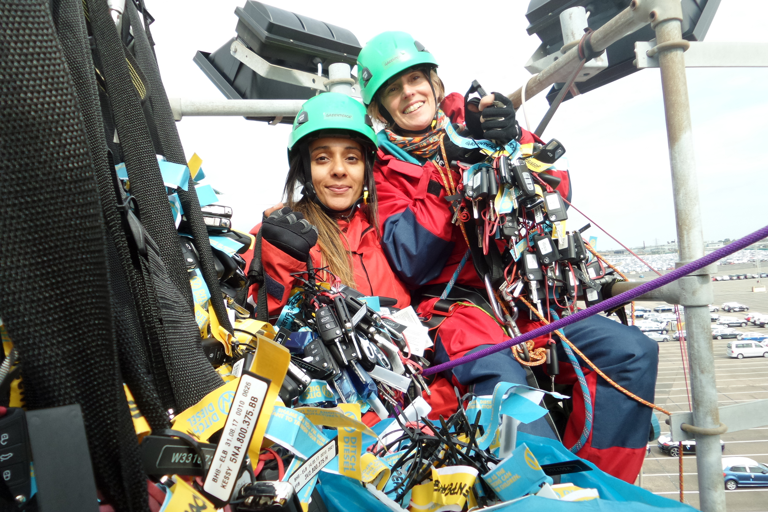 Meena and a white woman in climbing gear holding hundreds of car keys on a platform high over a dockside car park