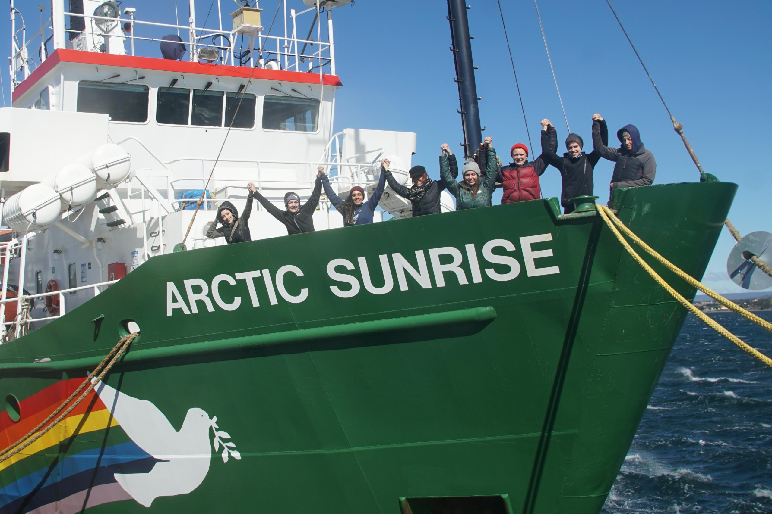 Meena with seven women standing on the front deck of the Actic Sunrise, a Greenpeace ship which is mostly green, with a dove and rainbow motif painted on it. Meena is the only person of colour.