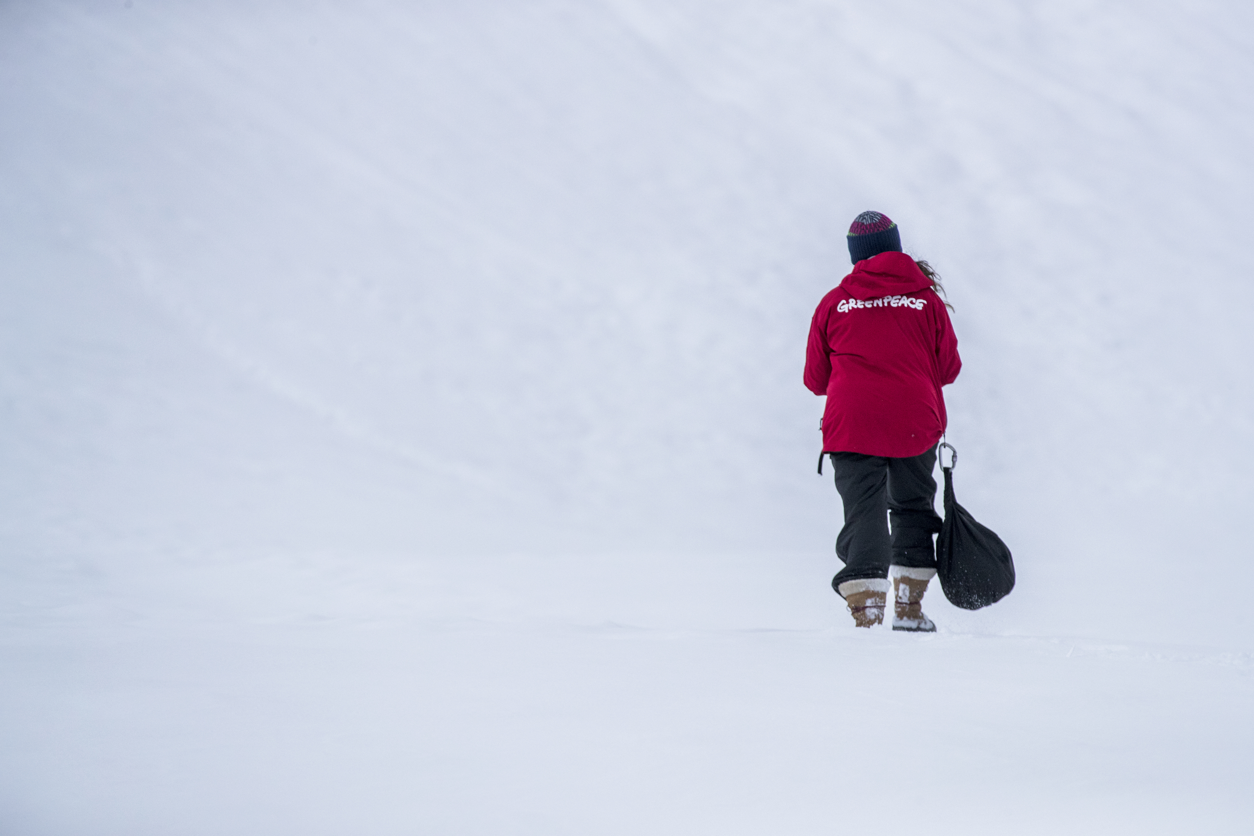 Meena walking alone in the distance in the Antarctic, surrounded by snow